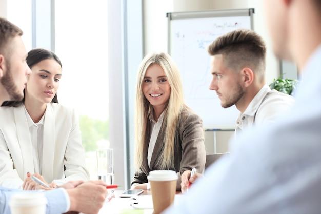 Группа деловых людей на встрече на фоне офиса. сосредоточьтесь на красивой блондинке