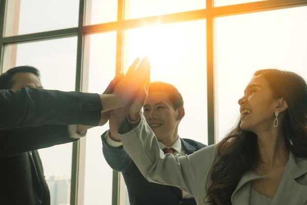 Группа деловых людей подняла руки вверх