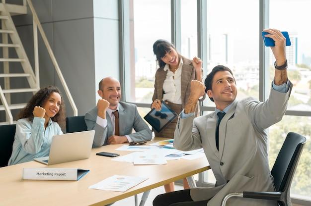Группа деловых людей, делающих селфи в офисе