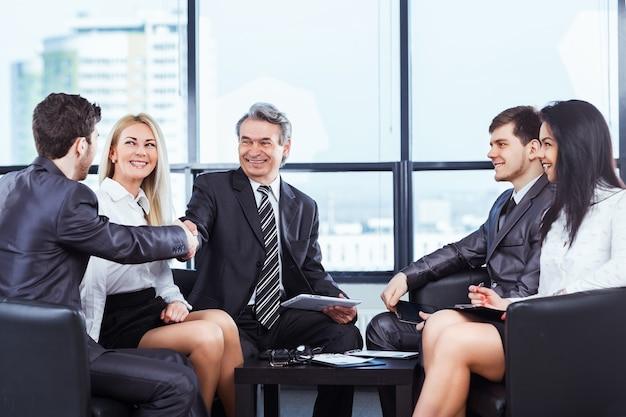 Группа бизнесменов обсуждает политику компании в офисе.