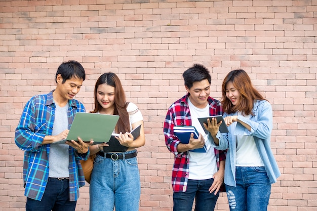 명랑하고 행복한 십대 그룹이 랩톱 및 태블릿에 대한 정보를 재미있게 살펴 보았습니다. 대학생 그룹 개념