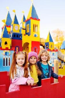 Группа веселых детей играет в парке развлечений на фоне красочного сказочного замка.