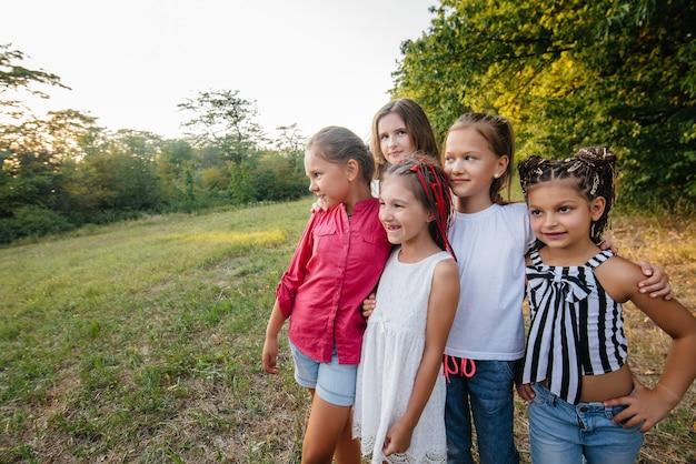 Группа веселых девушек улыбаются и играют в парке во время заката. детский летний лагерь.