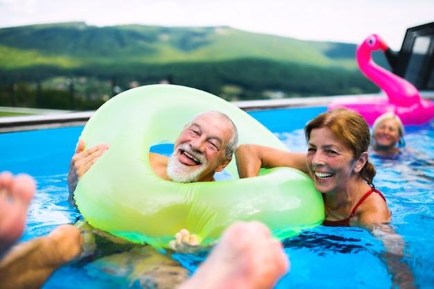 뒷마당에 있는 야외 수영장에서 즐거운 시간을 보내는 한 무리의 쾌활한 노인들.