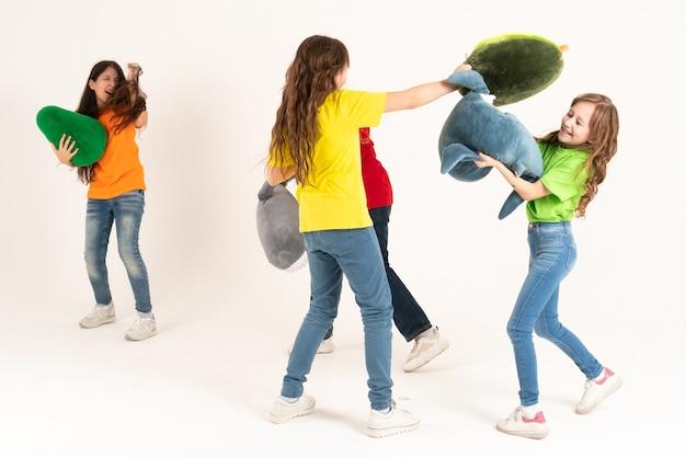 Группа детей в яркой одежде своими любимыми мягкими игрушками бьет друг друга подушками на белом фоне. всемирный день защиты детей
