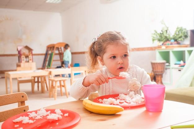 木製のテーブルに座ってご飯を食べる幼稚園の子供たちのグループ