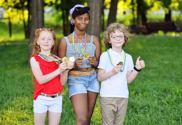 공원과 녹지를 배경으로 목에 메달을 두른 다양한 국적의 운동선수 어린이 그룹.