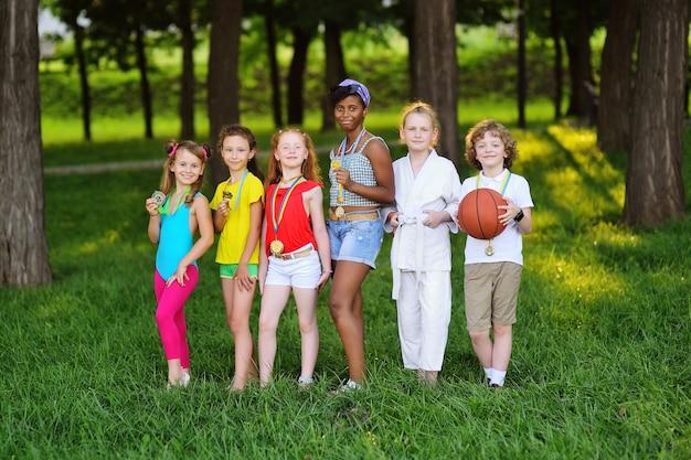 목에 메달이 달린 운동복을 입은 다양한 인종과 국적의 아이들이 녹지와 공원을 배경으로 웃고 있습니다.
