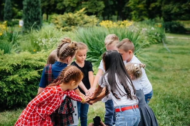 Группа детей бегает, развлекается и играет большой командой летом в парке. счастливое детство.