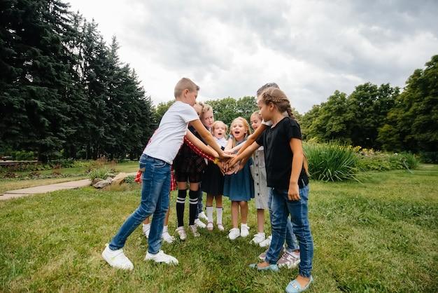 子供たちのグループが走り回って、楽しんで、公園で夏に大きなチームとして遊んでいます。幸せな子供時代。