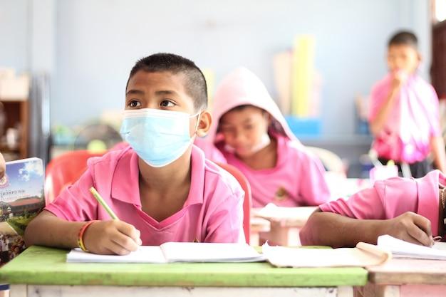 教室に座って書いている子供たちのグループ。