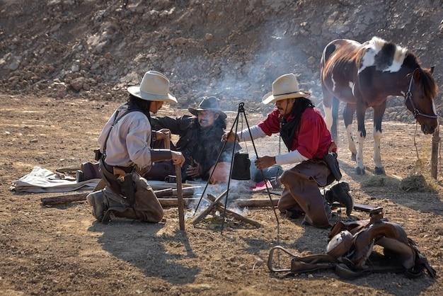 キャンプでリラックスするために座って、コーヒーを飲むカウボーイの男性のグループ