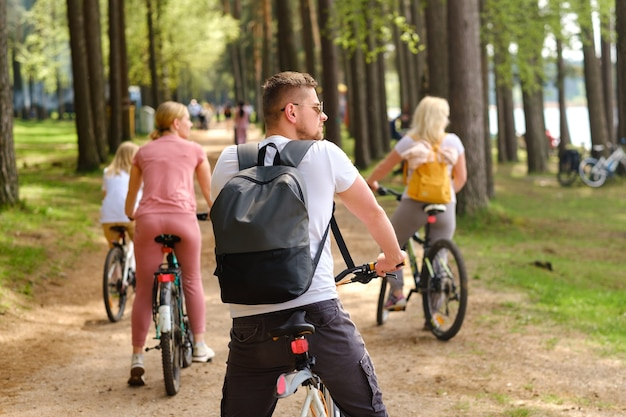 バックパックを背負ったサイクリストのグループが、自然を楽しむ林道を自転車で走ります。