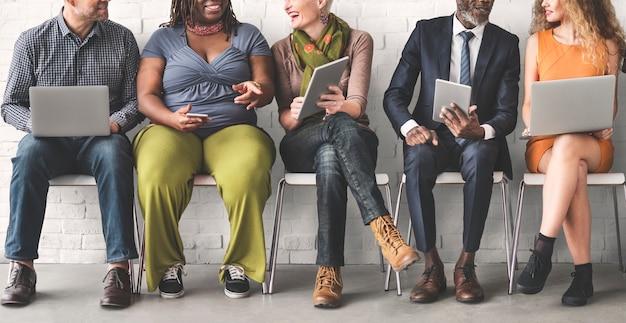 Группа различных людей использует цифровые устройства