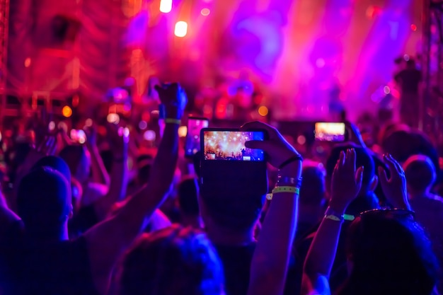 한 무리의 팬들이 음악 콘서트에서 손을 들었다