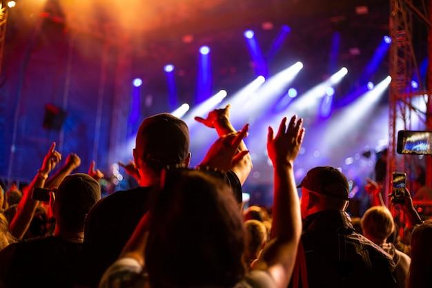 한 무리의 팬이 음악 콘서트에서 손을 들었습니다.소프트 포커스 흐림