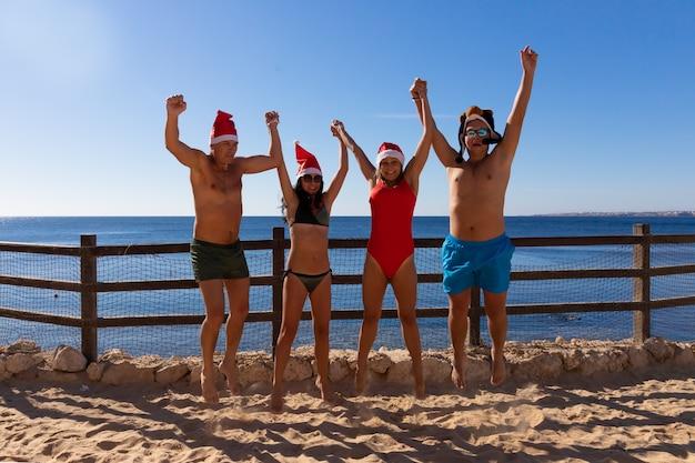 수영복과 빨간 크리스마스 모자를 쓴 4 명의 그룹이 홍해 해변에서 크리스마스와 새해를 축하합니다.