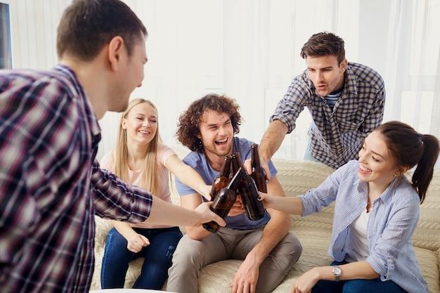 Группа друзей звенит бутылками на встрече в комнате