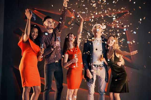 Группа друзей развлекается в красивых шифоновых платьях с шампанским и конфетти, готовясь к новому году