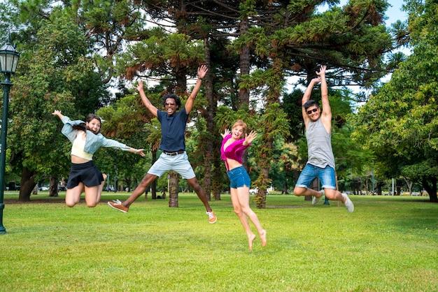 幸せで公園でジャンプしている友人のグループ