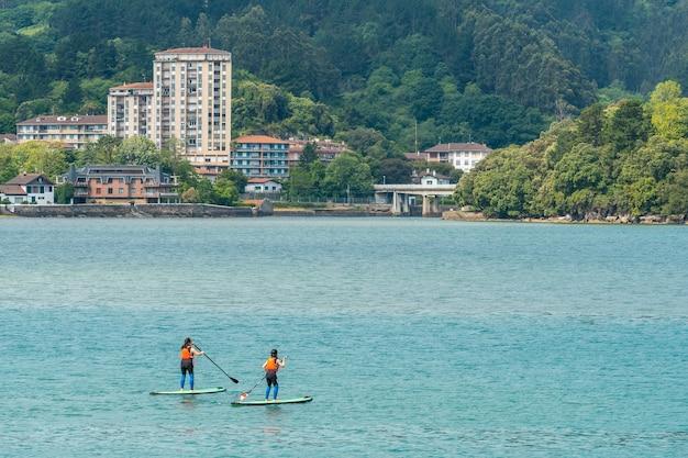 ムンダカの隣にあるビスカヤ生物圏保護区であるウルダイバイの海でパドルサーフィンをしている友人のグループ。バスク