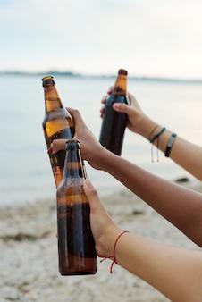 ビーチでビールを飲みながら、友達のグループ。夏のビーチパーティーをしている友人のグループ。