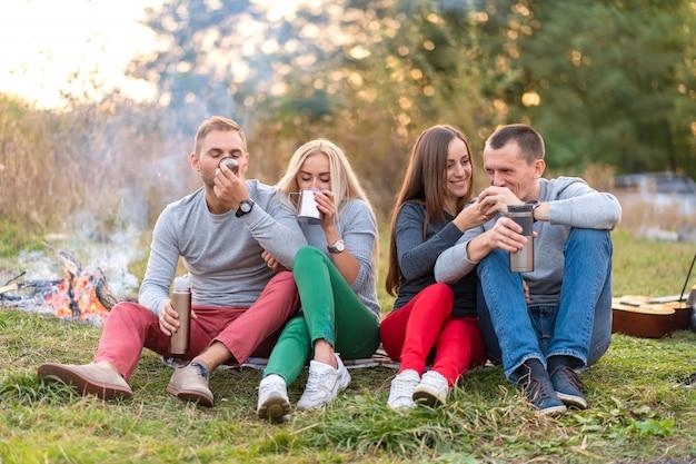 Группа друзей наслаждается согревающим напитком из термоса в прохладный вечер у костра в лесу. весело провести время с друзьями