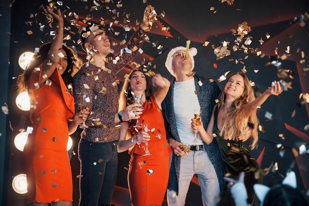 Группа друзей позирует и веселиться со снеговиками и шампанским. празднование нового года.