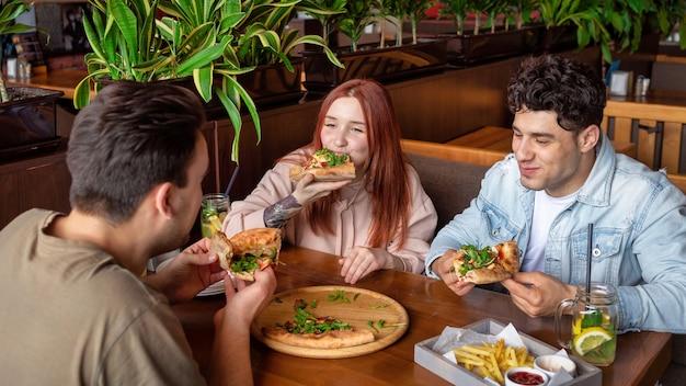 술집에서 쉬고있는 친구 그룹. 먹고, 마시고, 테이블에 음식. 우정