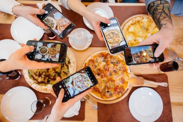 한 무리의 친구들이 블로그 피자가게를 위해 맛있는 피자를 클로즈업하여 사진을 찍고 있습니다.