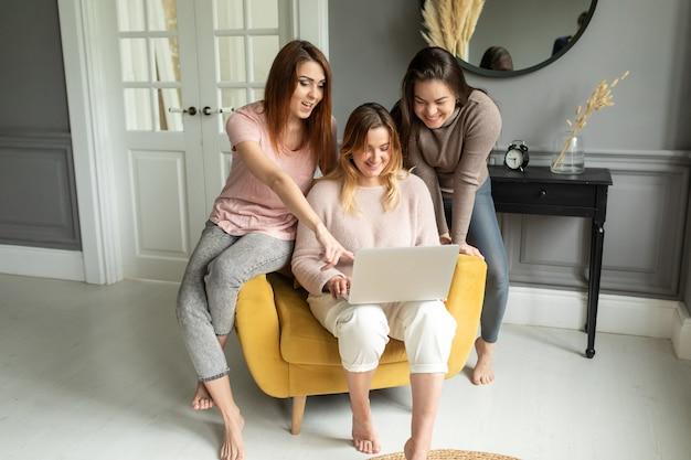 Группа подруг общается с другом по видеоконференции на ноутбуке. дружба