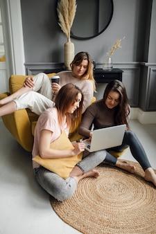 Группа подруг общается с другом по видеоконференции на ноутбуке