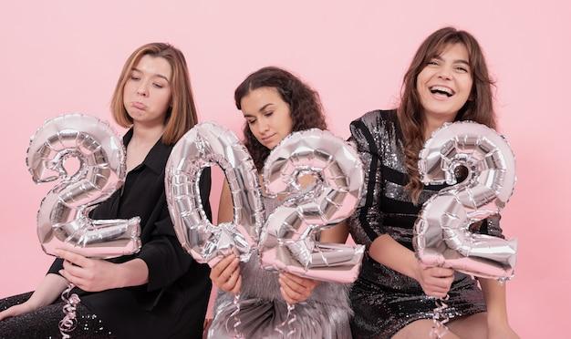 ピンクの背景に2022年の数字の形をした銀箔の風船を持ったガールフレンドのグループは、新年を祝ってさまざまな感情を経験しています。
