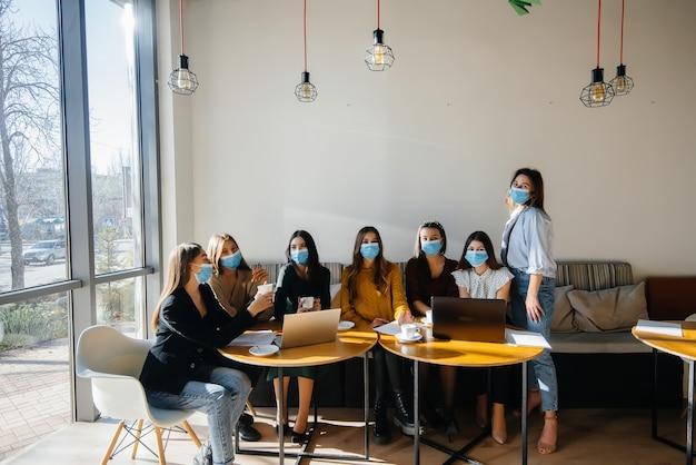 マスクをした女の子のグループがカフェに座ってノートパソコンで作業します。学生を教える。
