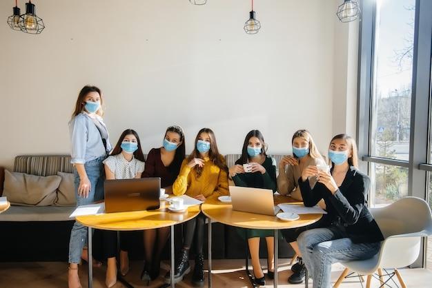 가면을 쓴 소녀 그룹이 카페에 앉아 노트북으로 작업합니다. 학생들을 가르치고 있습니다.