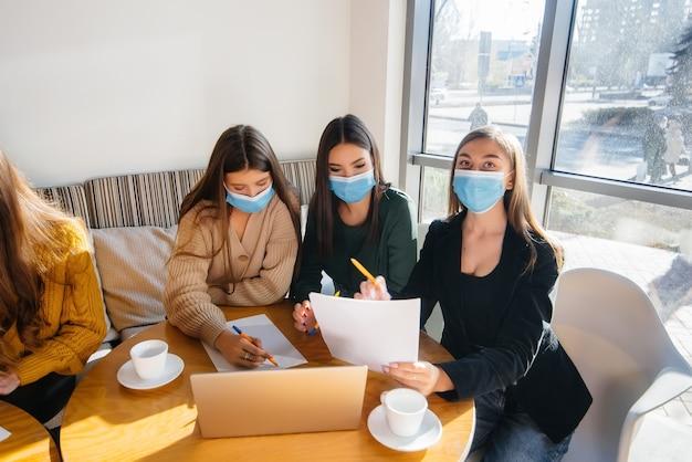 Группа девушек в масках сидят в кафе и работают на ноутбуках