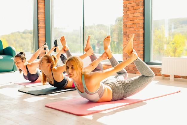 체육관에서 요가 연습하는 여자의 그룹. 영은 체육관에서 매트에 팔을 뻗은 여성에게 적합합니다.