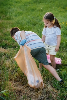해질녘에 아이들을 둔 한 무리의 소녀들이 공원에서 쓰레기 수거에 종사하고 있습니다. 환경 관리, 재활용.