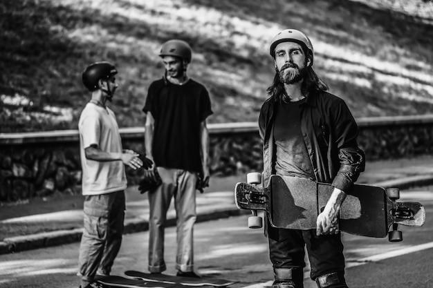 男のグループがロングボードに乗る。スケートボーダーの黒と白の肖像画。高品質の写真
