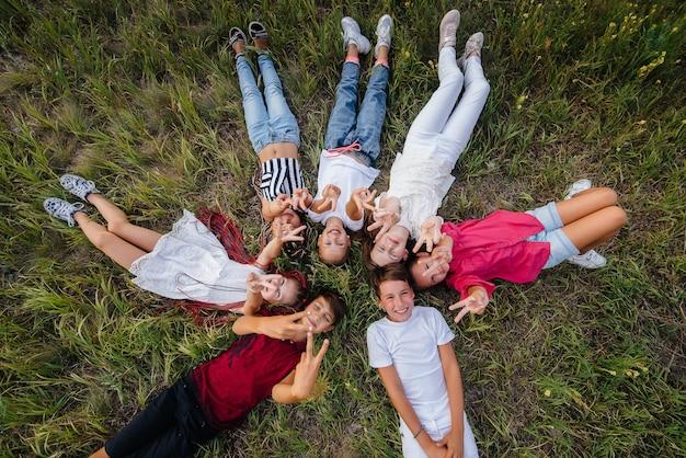 행복한 아이들의 그룹이 원 모양의 잔디에 누워 행복하게 웃고 있습니다. 행복한 어린 시절.