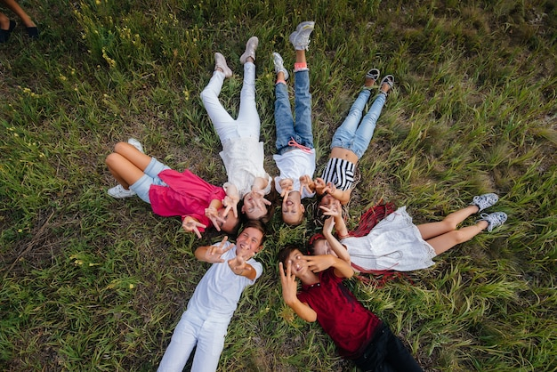 Группа счастливых детей лежат на траве в форме круга и счастливо улыбаются.