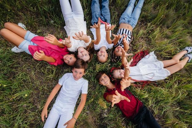 행복한 아이들의 그룹이 원 모양의 잔디에 누워 행복하게 웃고 있습니다.
