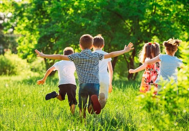 Группа счастливых детей мальчиков и девочек бегает в парке по траве в солнечный летний день.