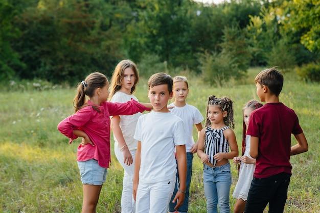 Группа счастливых детей бегают и играют в парке во время заката. летний детский лагерь.
