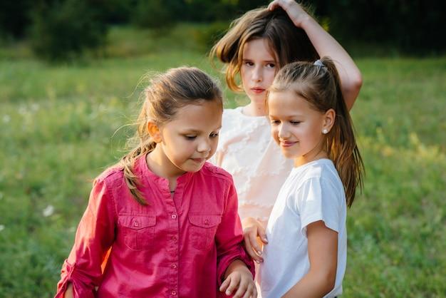 幸せな子供たちのグループは、日没時に公園で走って遊んでいます