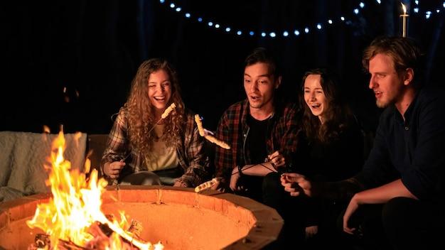 グランピングの夜にキャンプファイヤーの近くで幸せな若い友人のグループ