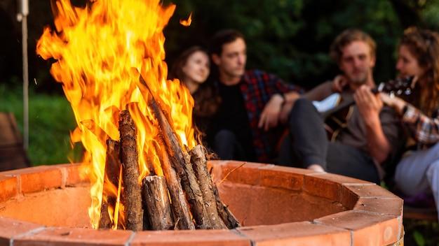 글램핑에서 모닥불 옆에 있는 행복한 젊은 친구들. 두 남자와 여자입니다. 기타 연주