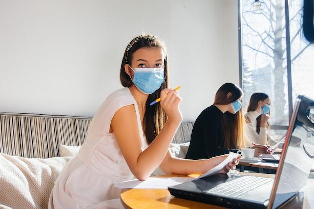 Группа девушек в масках сохраняет социальную дистанцию в кафе, работая за ноутбуком.