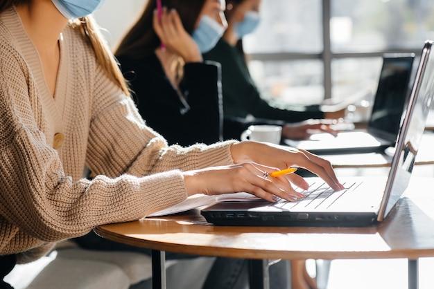 マスクされた女の子のグループは、ラップトップで作業しているとき、カフェで社会的な距離を保ちます。