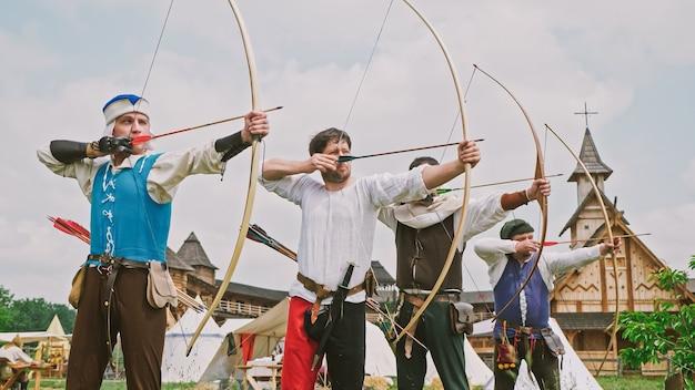 Группа средневековых лучников занимается стрельбой из лука.